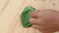 Closeup opening thai dessert was wrapped by banana leaves on wooden background Stock Footage