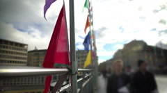 Colored flags waving in the wind on Lausanne bridge in Switzerland, urban life Stock Footage