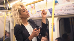 4K Young professional woman texting while traveling on subway train Stock Footage