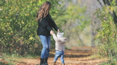 Mother turns baby outdoor. Autumn leaves background. Happy Family Values Stock Footage