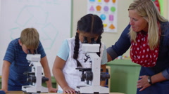 Teacher helping student with microscope in school classroom Arkistovideo