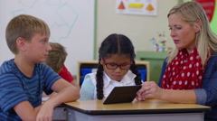 Teacher and students using digital tablet in school classroom Arkistovideo