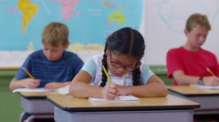 Students sitting at desks writing in school classroom Stock Footage