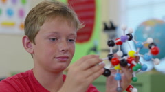 Young boy in school classroom building a molecule model in science class Stock Footage