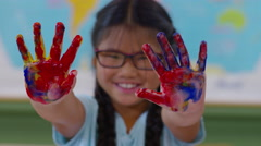 Young girl fingerpainting holds up messy hands Stock Footage