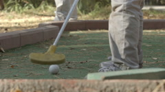 SLOW MOTION: Little boy tries to beat golf ball (back view) Stock Footage