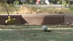 SLOW MOTION: Little player beats a golf ball to hole Stock Footage