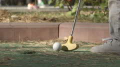 SLOW MOTION: Little player beats a golf ball to hole course Stock Footage