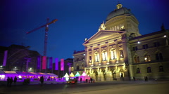 People walking near illuminated Federal Palace and ice rink in Bern, Switzerland Stock Footage