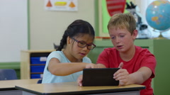 Two students work on digital tablet together in school classroom Stock Footage