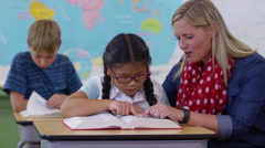 Teacher and student looking up word in dictionary together Stock Footage