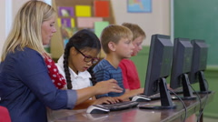 Teacher helping student with computer project in school classroom Stock Footage