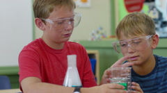 Two boys in school classroom working on science experiment Stock Footage