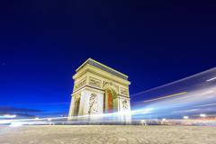 Arc de Triomphe and blurred traffic at night Stock Photos