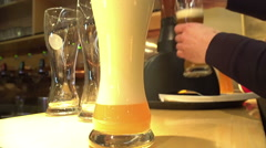 Barman pouring foamy beer into glasses, brewing business, catering service Stock Footage