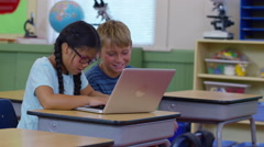 Two kids in school classroom working on laptop computer Arkistovideo