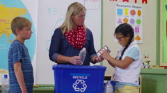 Teacher and students in school classroom putting bottles in recycle bin Stock Footage
