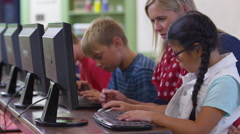 Teacher and student work on computer in school classroom Stock Footage