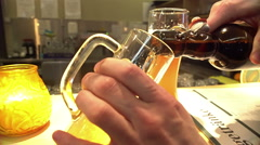 Pleased pub visitor pouring bottled beer into glass, weekend relaxation, holiday Stock Footage