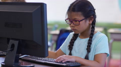 Young girl in school classroom workin on computer Stock Footage