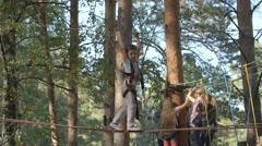 Little boy walks on a rope bridge in an adventure park - side view Stock Footage