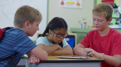 Three students having fun playing on digital tablet Arkistovideo