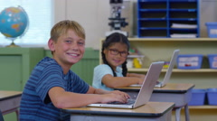 Portrait of two kids in school classroom with laptop computers Stock Footage