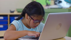 Portrait of young girl in school classroom with laptop computer Arkistovideo