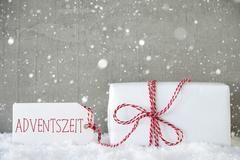 Gift, Cement Background With Snowflakes, Adventszeit Means Advent Season Stock Photos