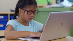 Girl in school classroom working on laptop computer Arkistovideo