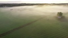 Cinematic flyover at foggy fields surrounded by Nordic forest landscape Stock Footage
