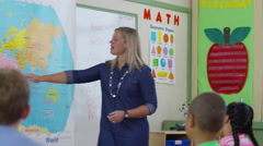 Teacher gives lesson in school classroom and students raise hands, rack focus Stock Footage