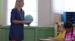 Teacher passing out papers in school classroom Stock Footage