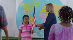 Teacher and student saying pledge of allegiance in school classroom Stock Footage