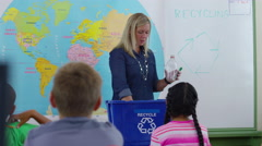 Teacher giving recycle lesson in school classroom Stock Footage