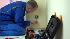 Electrician man with screwdriver tester test voltage on electric outlet socket Stock Footage