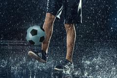 Water drops around football player Stock Photos