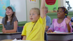 Students raise hands in school classroom Stock Footage