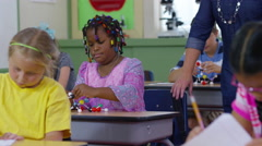 Teacher and student work on science model together in school classroom Stock Footage