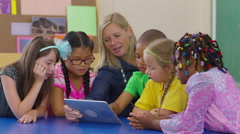 Teacher and group of students look at digital tablet together in school Stock Footage