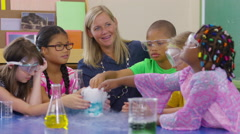 Teacher and group of students make a science experiment in school classroom Stock Footage