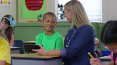 Teacher and student look at digital tablet in school classroom Stock Footage