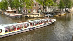 General view of an Amsterdam tour boat travelling through the canal Stock Footage