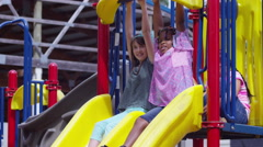 Girls going down slide on school playground Stock Footage