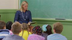 Teacher reads book to kids in school classroom Arkistovideo