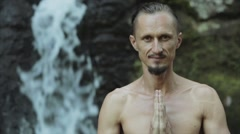 Young man practicing yoga fitness exercises outdoors on a jungle background. Stock Footage