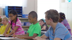 Student writes on board in school classroom Stock Footage