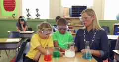 Teacher and students doing science experiment in school classroom Stock Footage