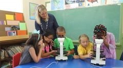 Teacher and students look through microscopes in school classroom Stock Footage