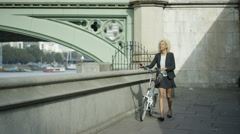 4K London businesswoman with bicycle making phone call outdoors in the city Stock Footage